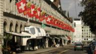 T/L MS Traffic on Rue de la Corraterie with flags trams, Geneva, Switzerland