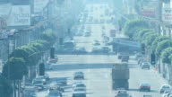 Traffic on six lane roadway lined w/ many light poles trees four cross street intersections in smog BG Air pollution Gasoline emissions Greenhouse...
