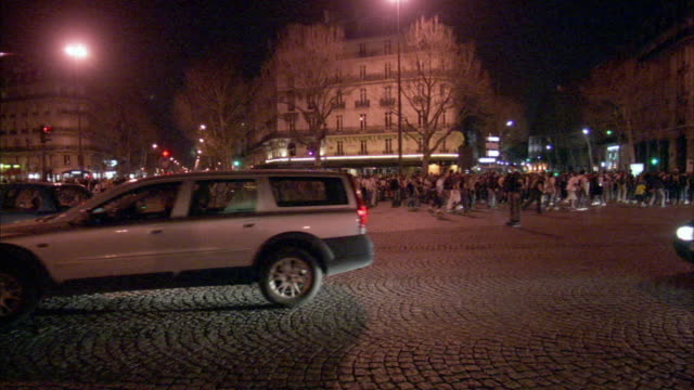 WS Traffic on street, crowd of roller skaters in background, night, Paris, France