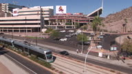 WS HA Traffic on street with METRO light rail passing by, Sun Devil Stadium at Arizona State University, home of Arizona State Sun Devils in background / Tempe, Arizona, USA