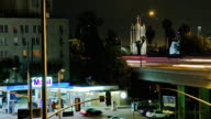 T/L MS Traffic on US Route 101 Hollywood Freeway above gas station, church in background, night, Hollywood, California, USA