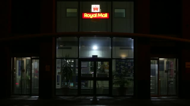 Traffic passes a Royal Mail Group Ltd buildling at night in Manchester UK on Tuesday Oct 8 Tilt down from sign to employee entering building Pan from...