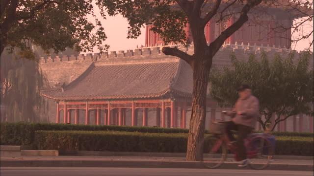 Traffic passes in front of watchtower at corner of Forbidden City, Beijing, China.