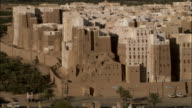 Traffic passes near a partially collapsed building in the mud-brick town of Shibam in Yemen.
