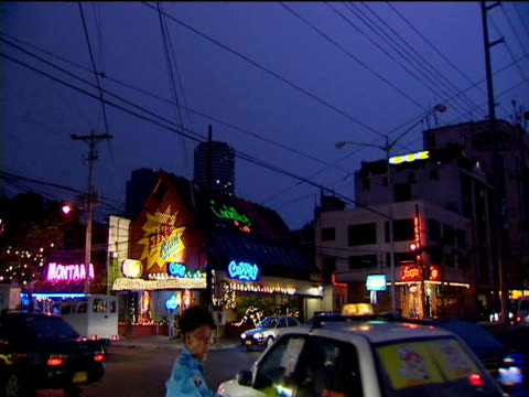 Traffic Policeman directs heavy flow of traffic flashing neon signs all around Manila