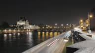 Traffic rushes beside the Seine at night while the Louvre shines in the background.
