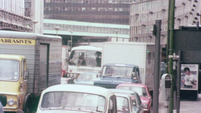 1976 MONTAGE Traffic snarling up on a busy city street surrounded by high-rise buildings / Birmingham, England, United Kingdom