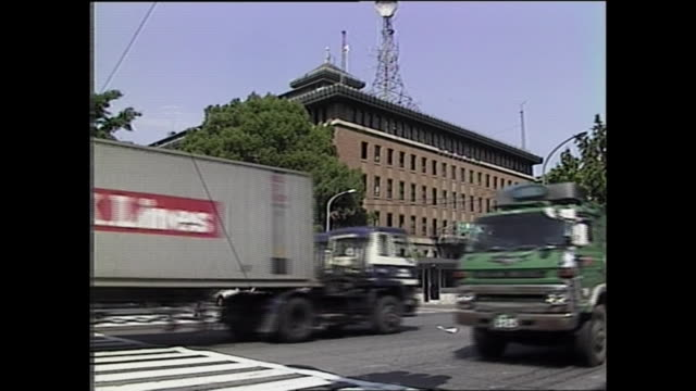 Traffic speeds past the Kanagawa Prefectural Government Office building / Shot at Yokohama on July 8 1987