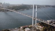 AERIAL Traffic traveling across a suspension bridge spanning the Bosphorus Strait / Istanbul, Turkey