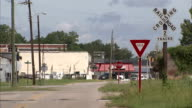 Traffic travels on a road near a stop sign, yield sign and railroad crossing sign. Available in HD.