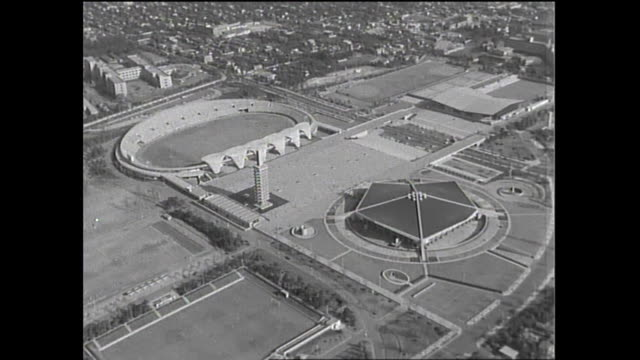 Traffic travels past the Komazawa Olympic Park contains Athletic Field and Gymnasium Building / Shot at Setagaya area in Tokyo on October 5 1965