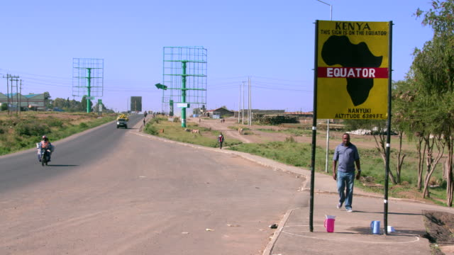 Traffic With Man Crossing The Equator Sign Nanyuki  Kenya