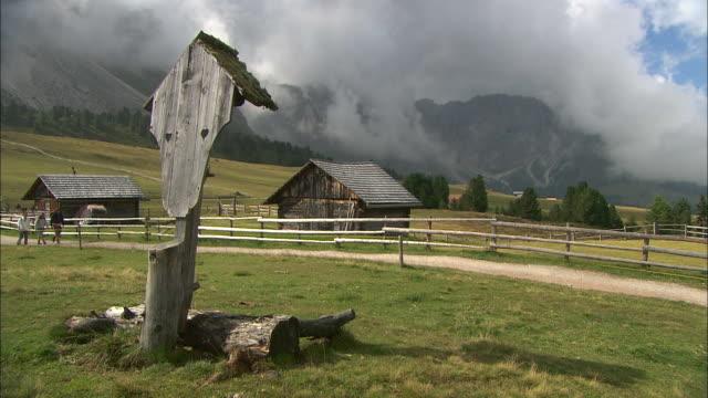 Trail between barns and wayside cross