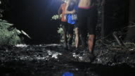 Trail run competitors running across a muddy road at night