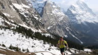 Trail runner ascends steep mountain slope, snow capped peaks above