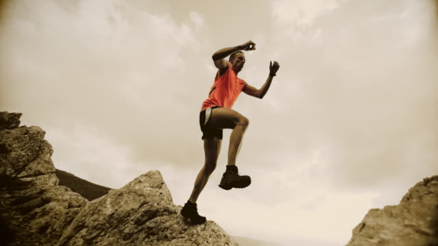 SLO MO trail runner jumping from the rock