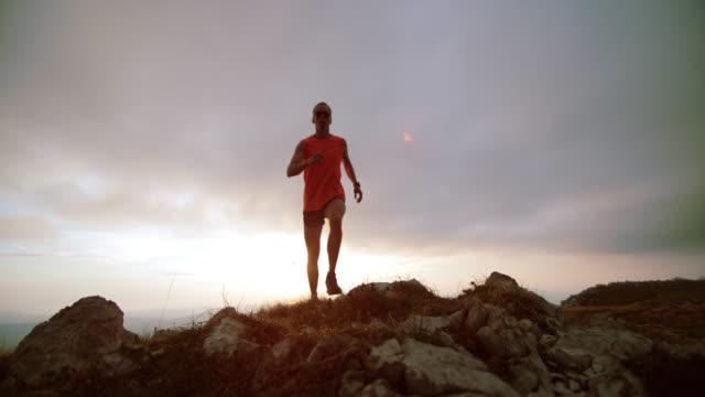SLO MO trail runner corre sulla ridge al tramonto