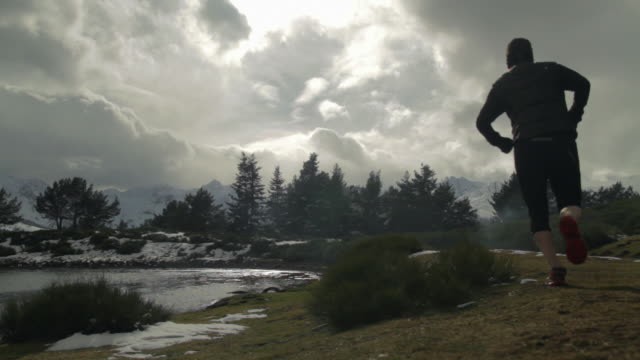 Trail runner running on the shore of a lake in a snowy landscape amidst spectacular mountains