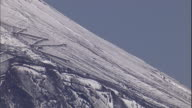 A trail zig-zags along a snow-dusted slope of Mt. Fuji.