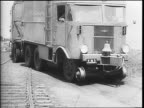 A trailer driving along the road toward the camera / the trailer's chassis are shown / a view of the trailer's air cylinders are shown / a rail wheel...