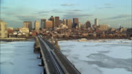 WS HA Train and traffic on Longfellow Bridge crossing frozen Charles River, city skyline in background / Boston, Massachusetts, USA