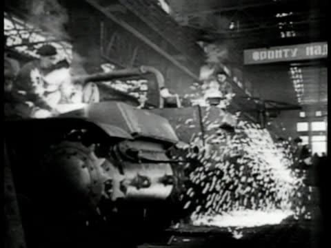 Train crossing Russian border guard XWS Factory smoke stacks INT VS Workers welding building armored tanks tank gun parts artillery shells on...