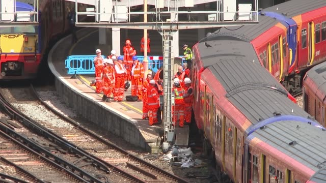 Train derails at Waterloo station causing delays Various of workers on tracks by derailed train