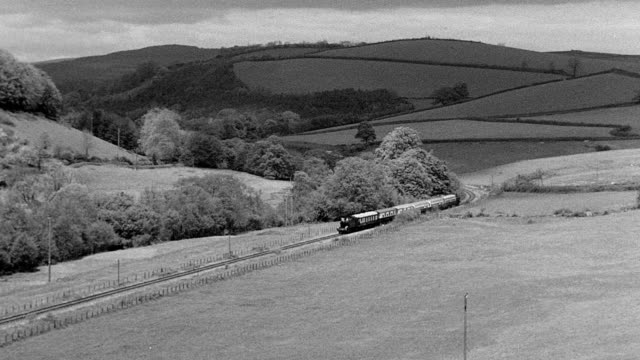 1969 MONTAGE Train moving along the Dart Valley Railway in the countryside / Devon, England, United Kingdom