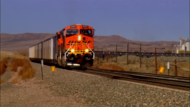 BNSF train moving slowly toward camera / zoom out wide shot of landscape beyond train tracks / Sheridan, Wyoming