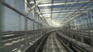 POV Train on elevated monorail track passing through modern glazed tunnel / Tokyo, Tokyo Prefecture, Japan