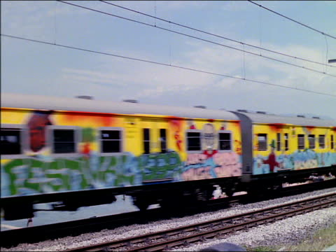 Train painted in bright colours passes to reveal seaside, South Africa