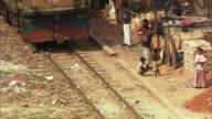 HA, MS, Train passing by children and men standing near huts in shanty town, Dhaka, Bangladesh