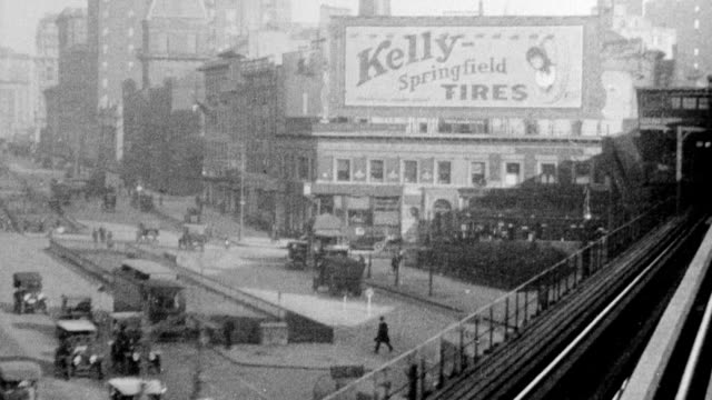 POV train passing 'Kelly Tires' building turning curves / train passes Hippodrome Theater / views of neighborhoods passing people at stations in New...