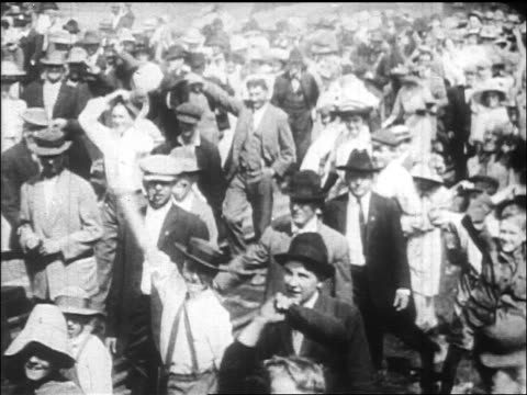 B/W 1912 train point of view away from crowd walking on tracks waving / documentary