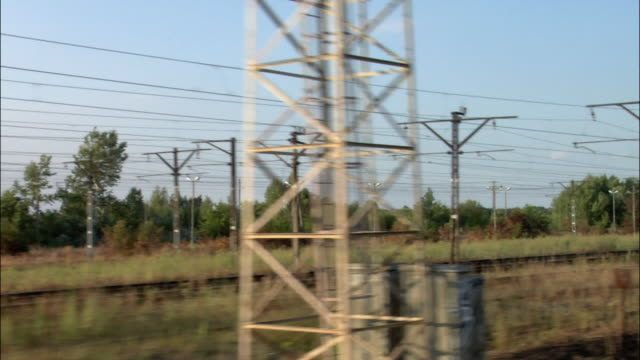 Train point of view passing power lines / passing storage containers on freight train / Krakow, Poland