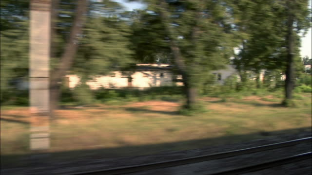 Train point of view passing train traveling in opposite direction through residential area / passing houses and light traffic