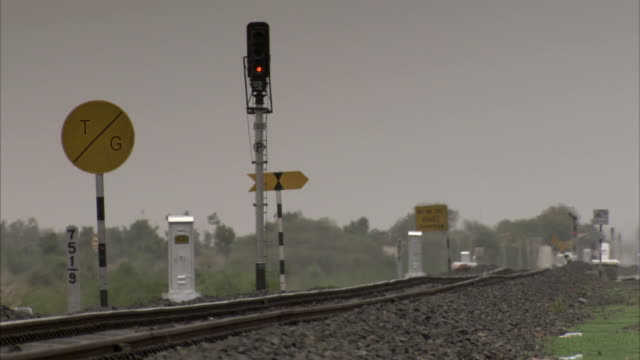 Train signals line the side of a railroad track. Available in HD.