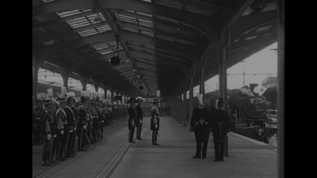 Train station platform with large number of military all in plumed or feathered hats formal uniforms / Emperor Hirohito waits on platform as steam...