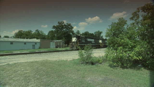 PAN Train traveling down railroad tracks in rural town / Columbia, South Carolina, United States
