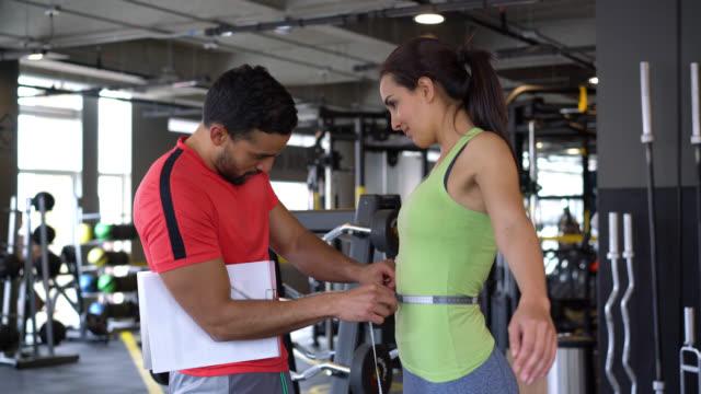 Trainer in de sportschool een taille van klanten te meten