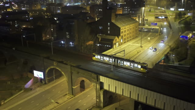Trains passing at night in the city, with view over city - Manchester aerial footage