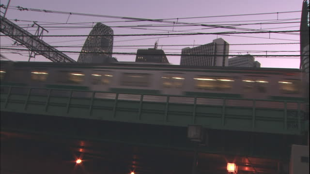 Trains, traffic, and pedestrians move along busy streets in Tokyo.
