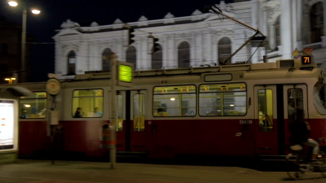Tram at night exiting station outside Burg Theatre.Pan L to R.