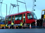 Tram carriage on show on Southbank Vars of workmen hoisting tram carriage into position with aid of crane
