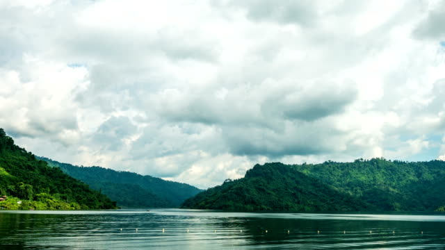 Tranquil scene of lake and moving cloudy with green mountain background