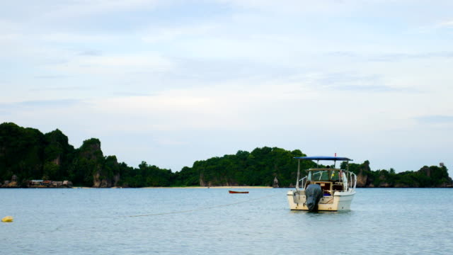 Tranquil scene of moored speed boat with tropical green island background