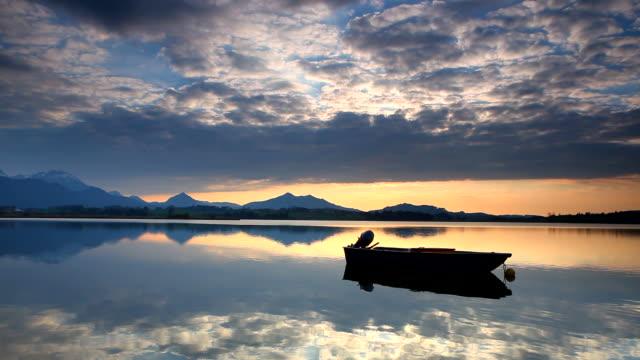tranquil sunset at lake hopfensee, bavaria, boat, germany