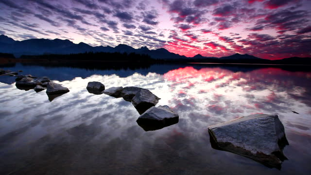 tranquil sunset at lake hopfensee in bavaria with rocks- germany