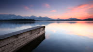 tranquil sunset at lake with jetty in bavaria - germany