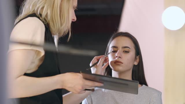 Transgender make-up artist applying bronze eyeshadow on female client